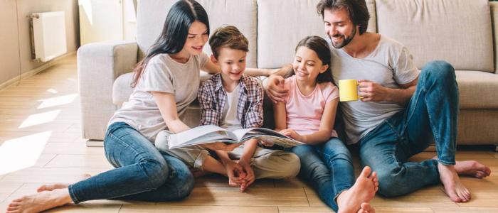 une famille avec 2 enfants en train de lire un magazine