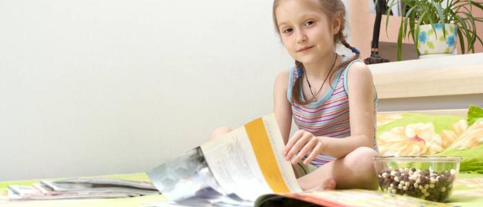 petite fille en train de lire un magazine pour enfant