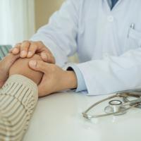 médecin qui serre la main d'une patiente pour lui annoncer une fausse couche