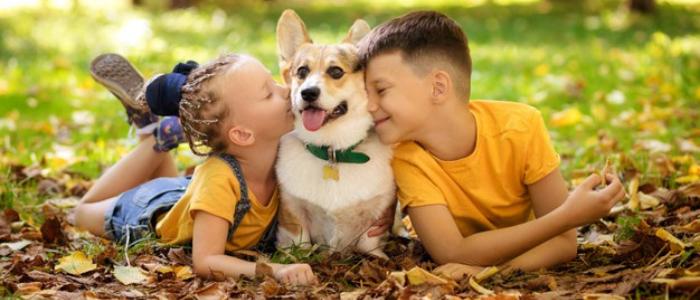 une petite fille et un petit garçon en train de faire un câlin à un petit chien
