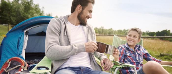 un père et son fils au camping sur des chaises pliantes