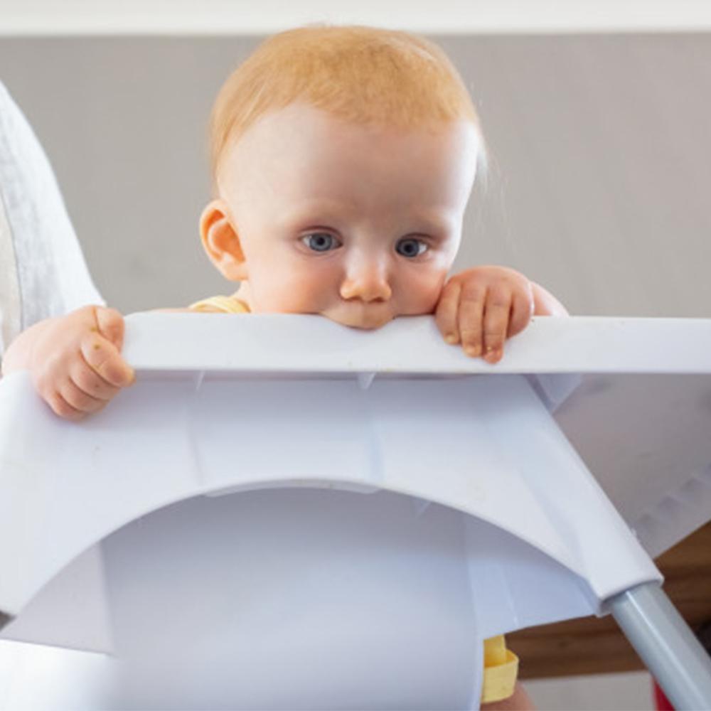 bébé met sa chaise haute à la bouche